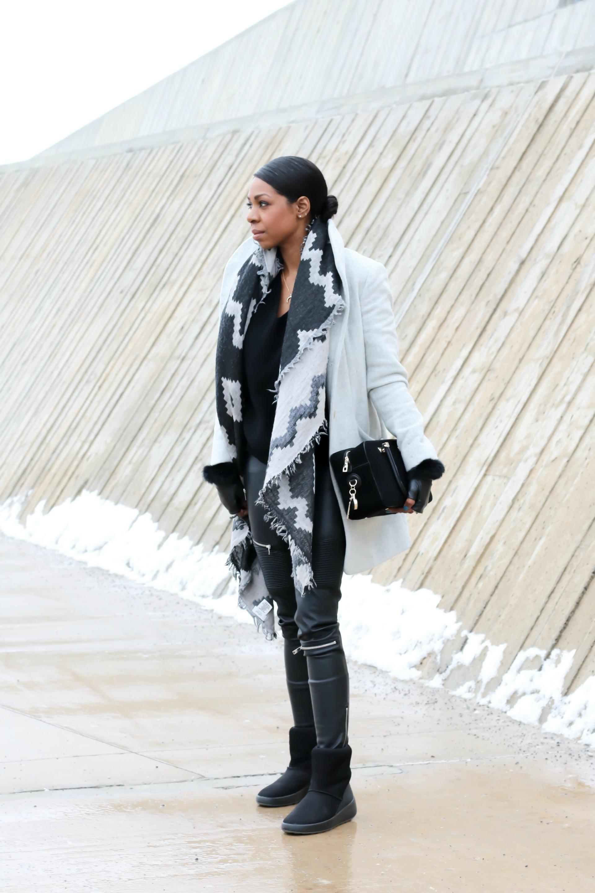 Image of Dom wearing a grey wool coat and black leather pants holding a suede purse on a cold winter's day