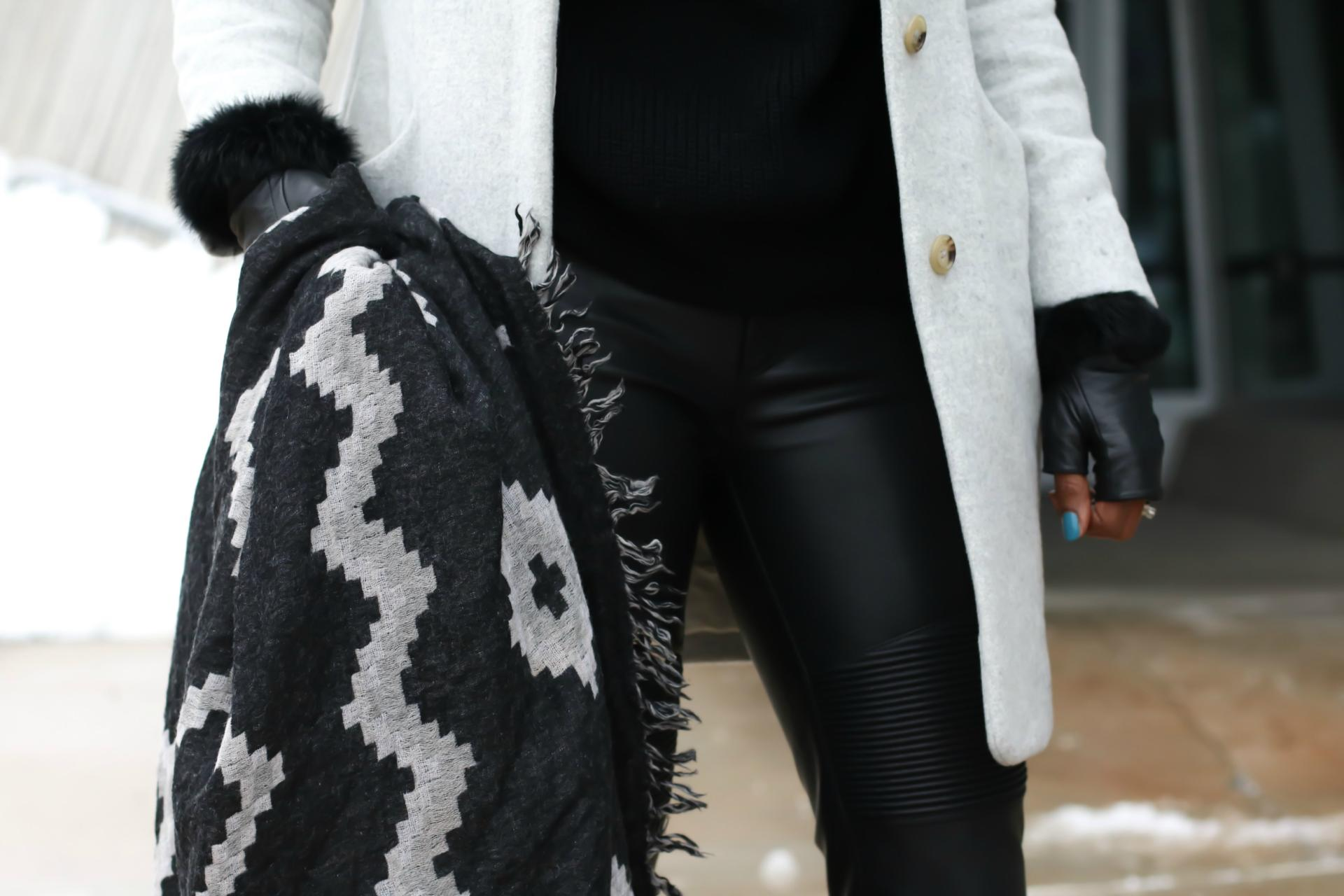 Image of Dom holding an Aritzia diamond mosaic blanket scarf in black and grey