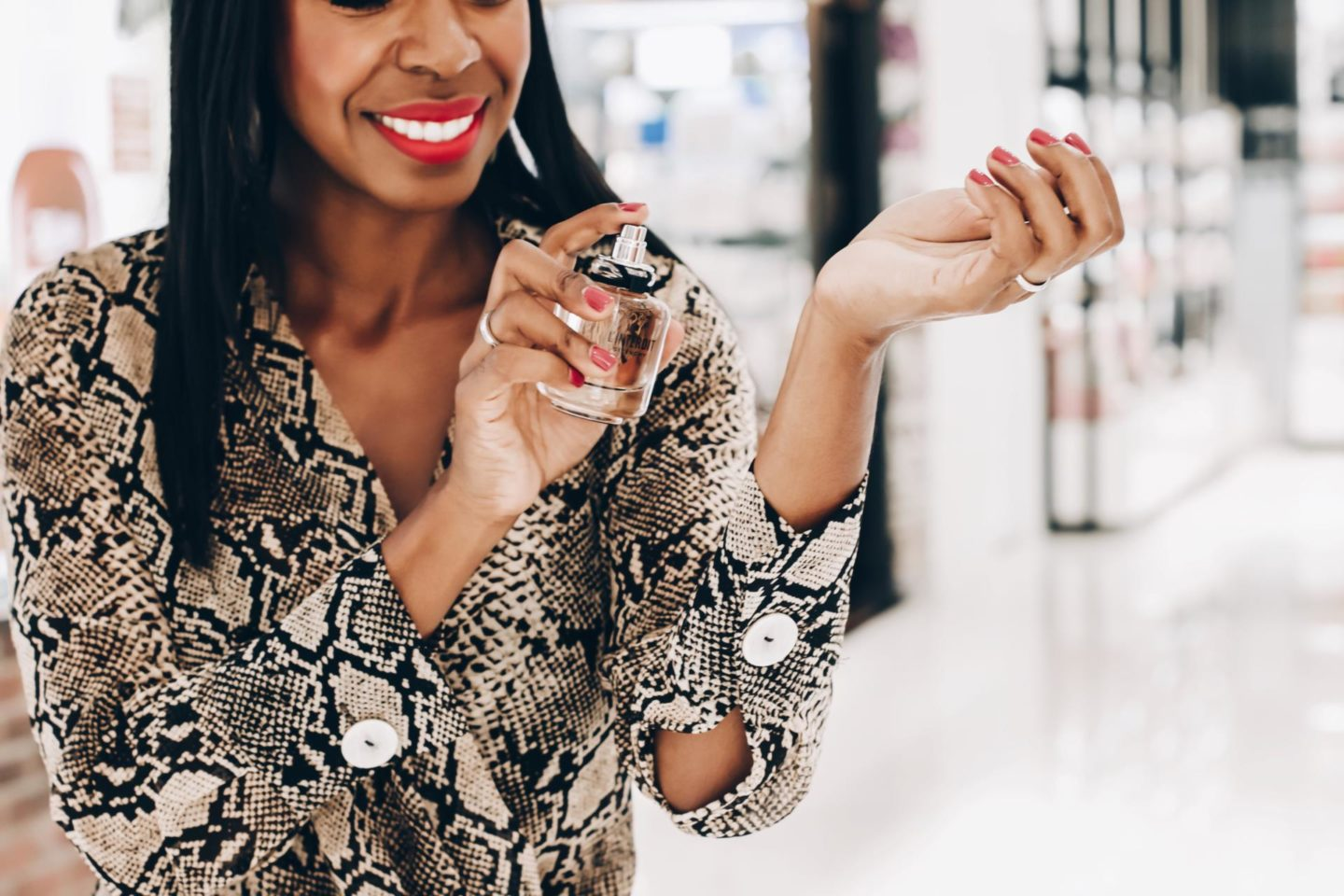 Dominique Baker spraying perfume on her wrist