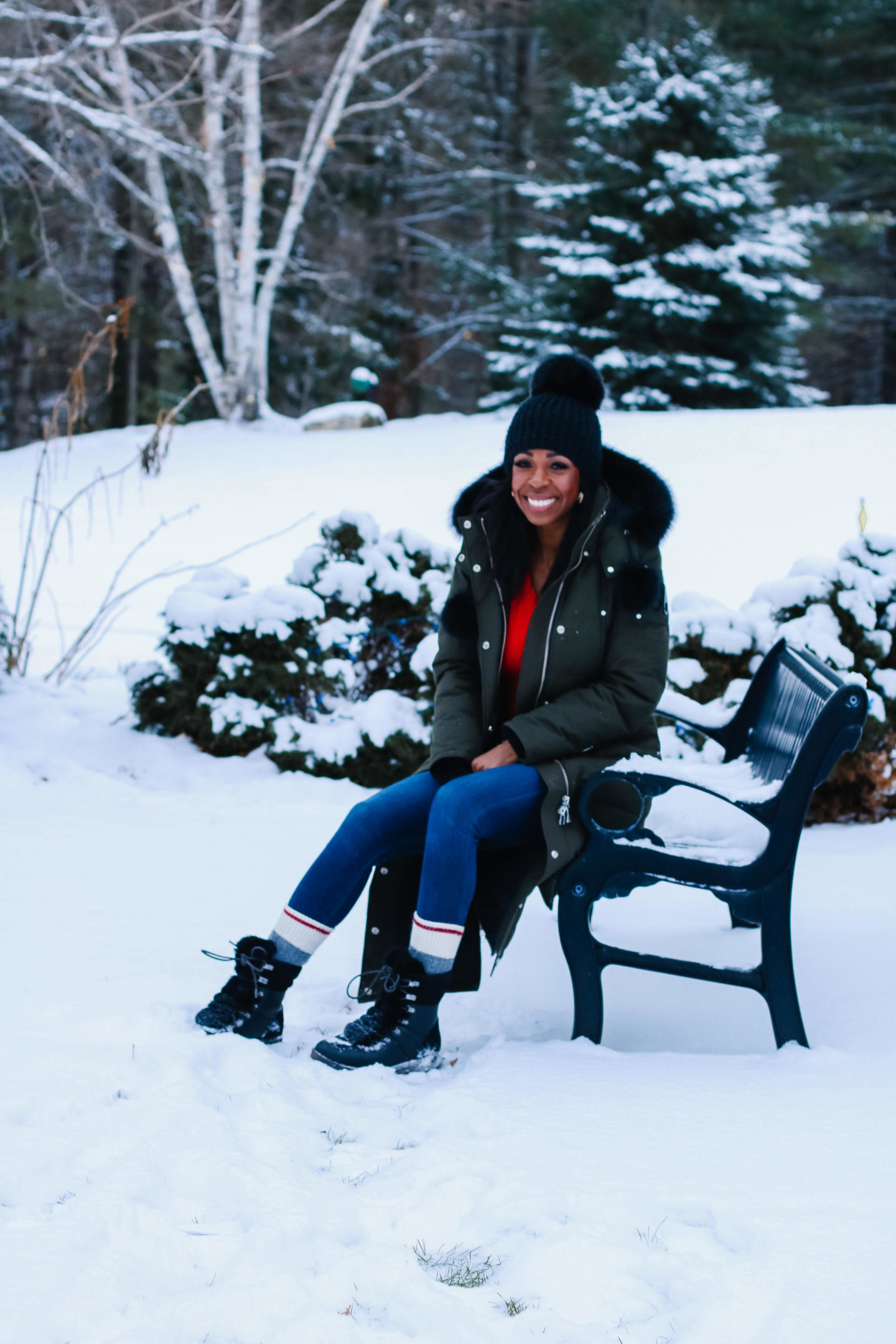 Dominique Baker Sitting on a bench in the forest wearing a Mooseknuckles parka