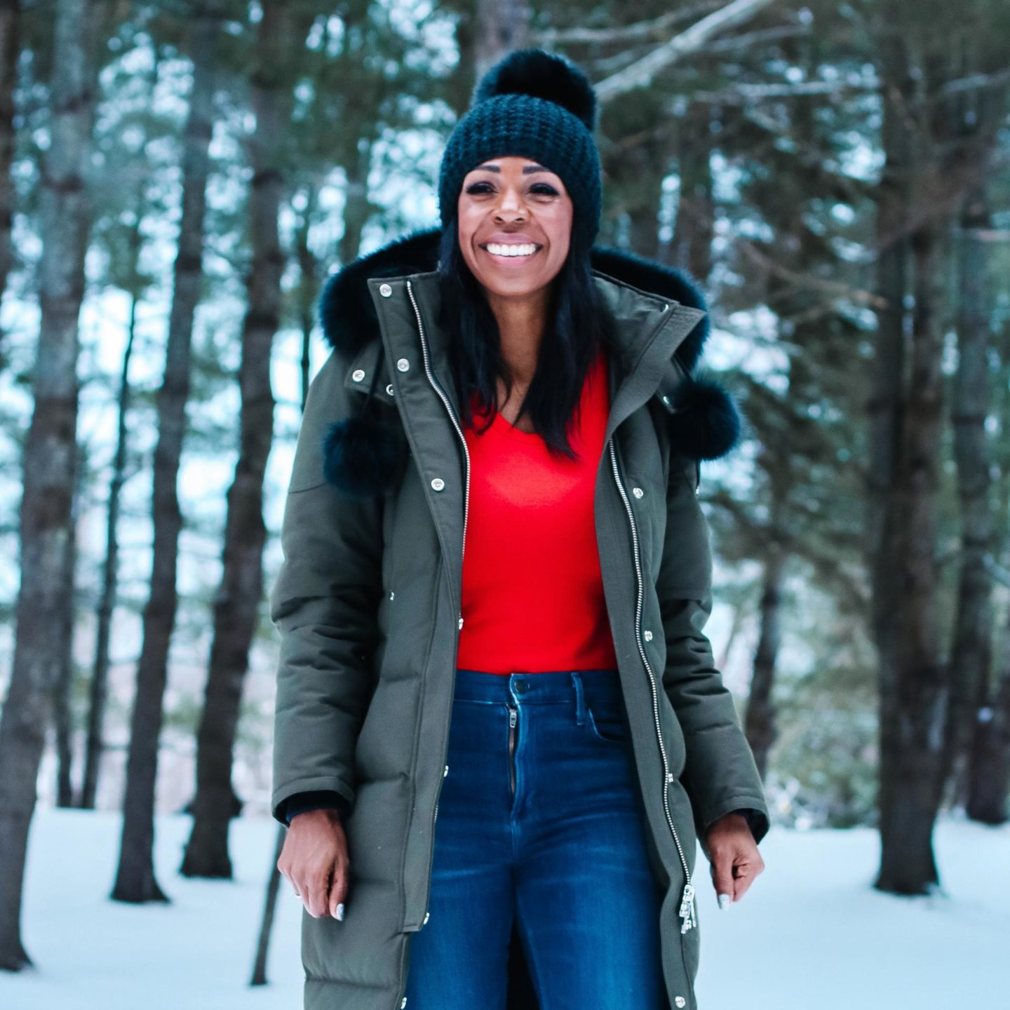 Dominique Baker walking and smiling in the forest wearing a Mooseknuckles parka