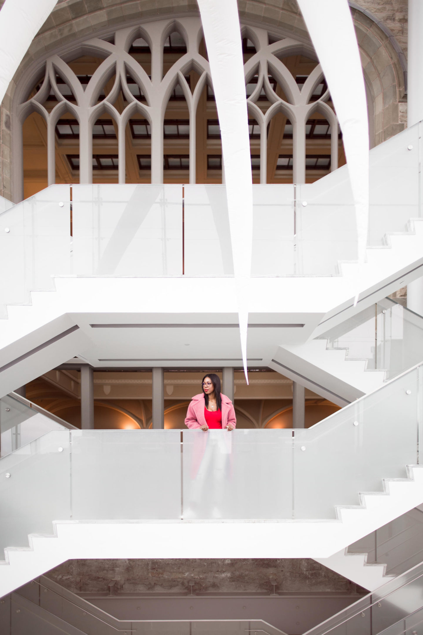 Dominique Baker standing on a grand staircase