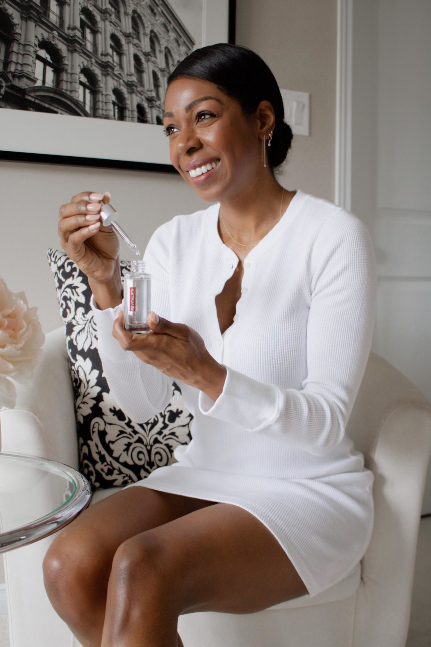 Dominique Baker Holding L'Oréal Revitalift Pure Hyaluronic Acid Serum White Dress sitting in chair