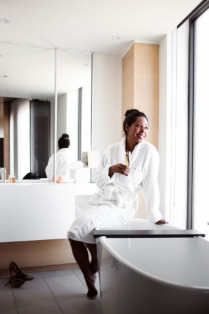 Dominique Baker sitting on edge of bathtub sipping Moët & Chandon