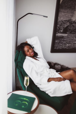 Dominique Baker lounging in a robe on a green velvet chaise longue at The Hotel Le Germain Ottawa