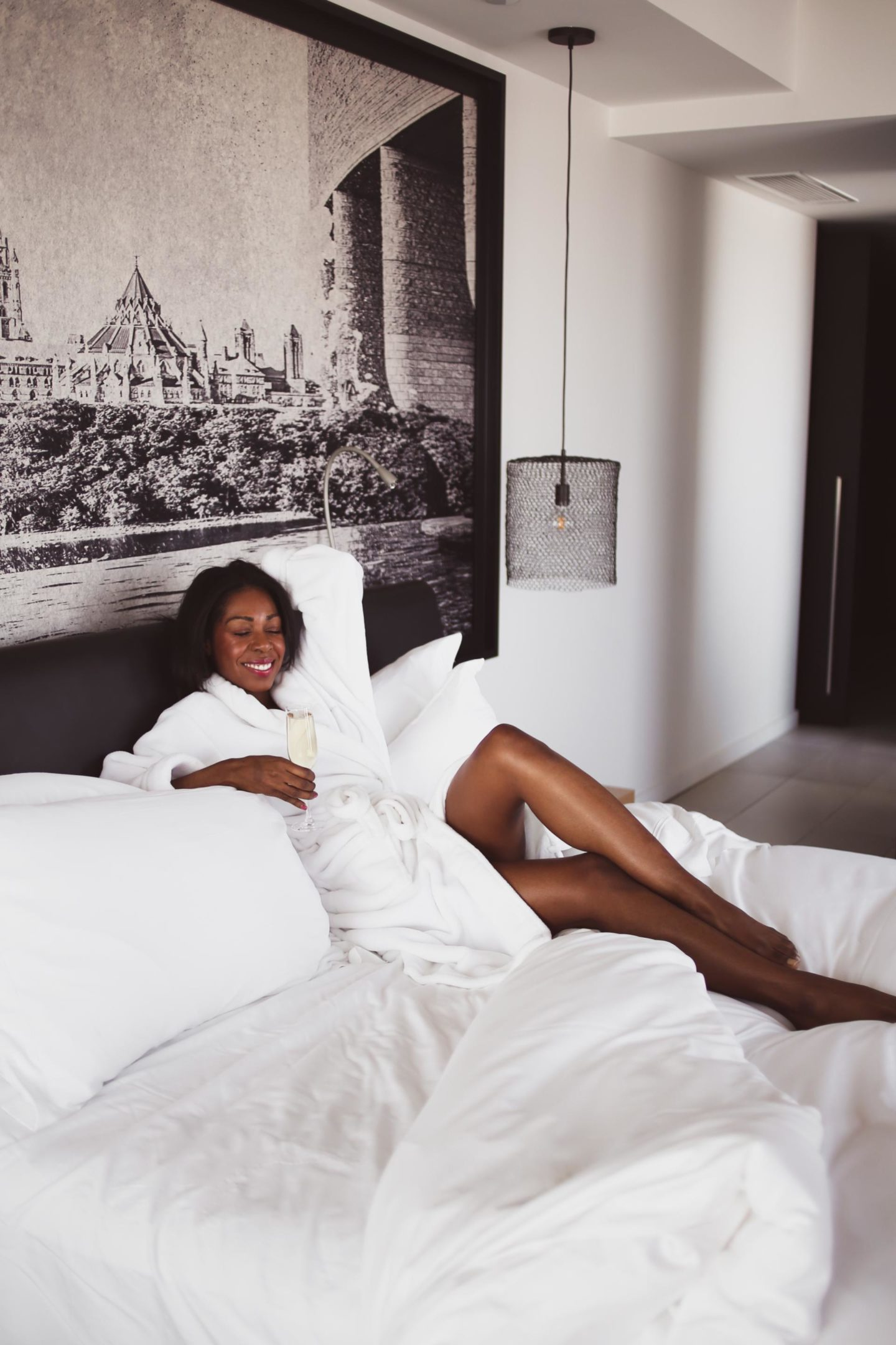 Dominique Baker lying in bed holding a glass of champagne at the Hotel Le Germain in Ottawa