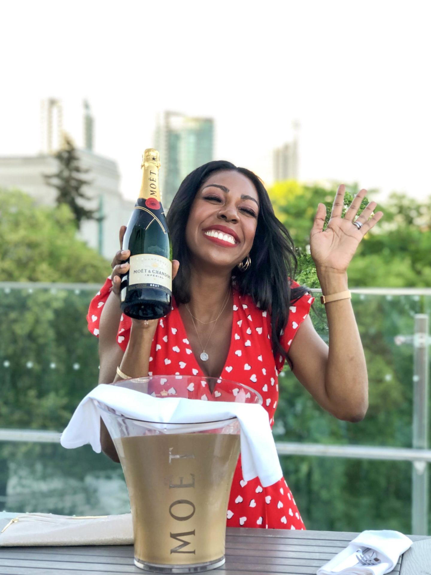 Dominique Baker holding a bottle of Moët & Chandon Champagne