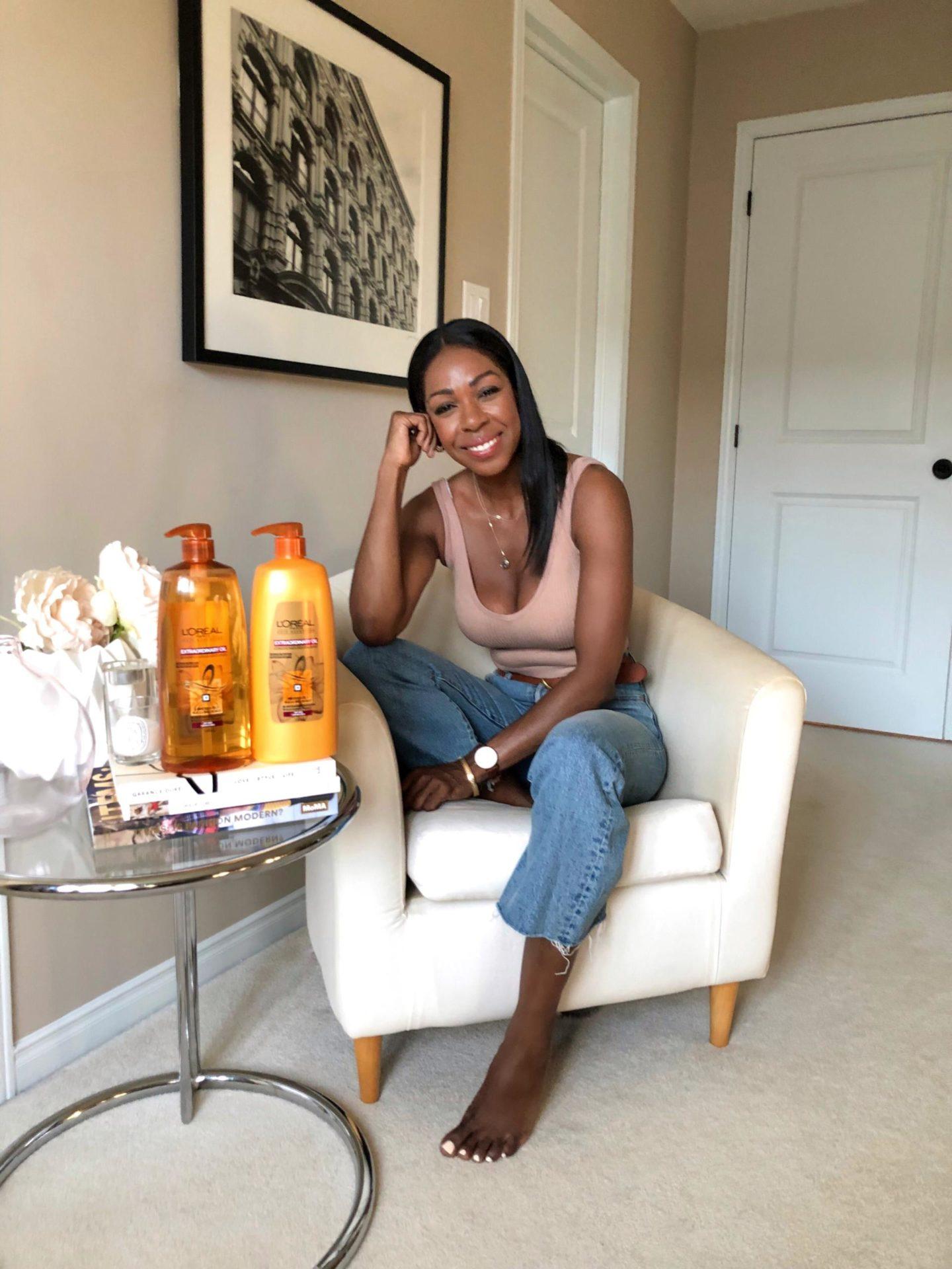 Dominique Baker Sitting with Bottles of L'Oréal Paris Extraordinary Oils Shampoo