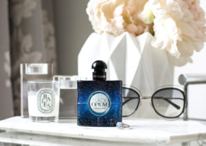 YSL Black Opium Perfume Bottle on vanity with Chloe sunglasses and candles