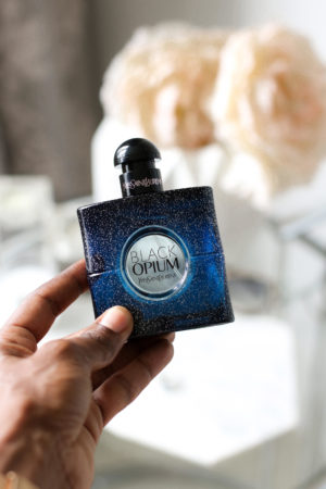 Dominique Baker holding bottle of YSL Black Opium Perfume