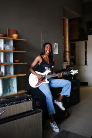 Dominique Baker playing electric guitar and singing at Metro Music