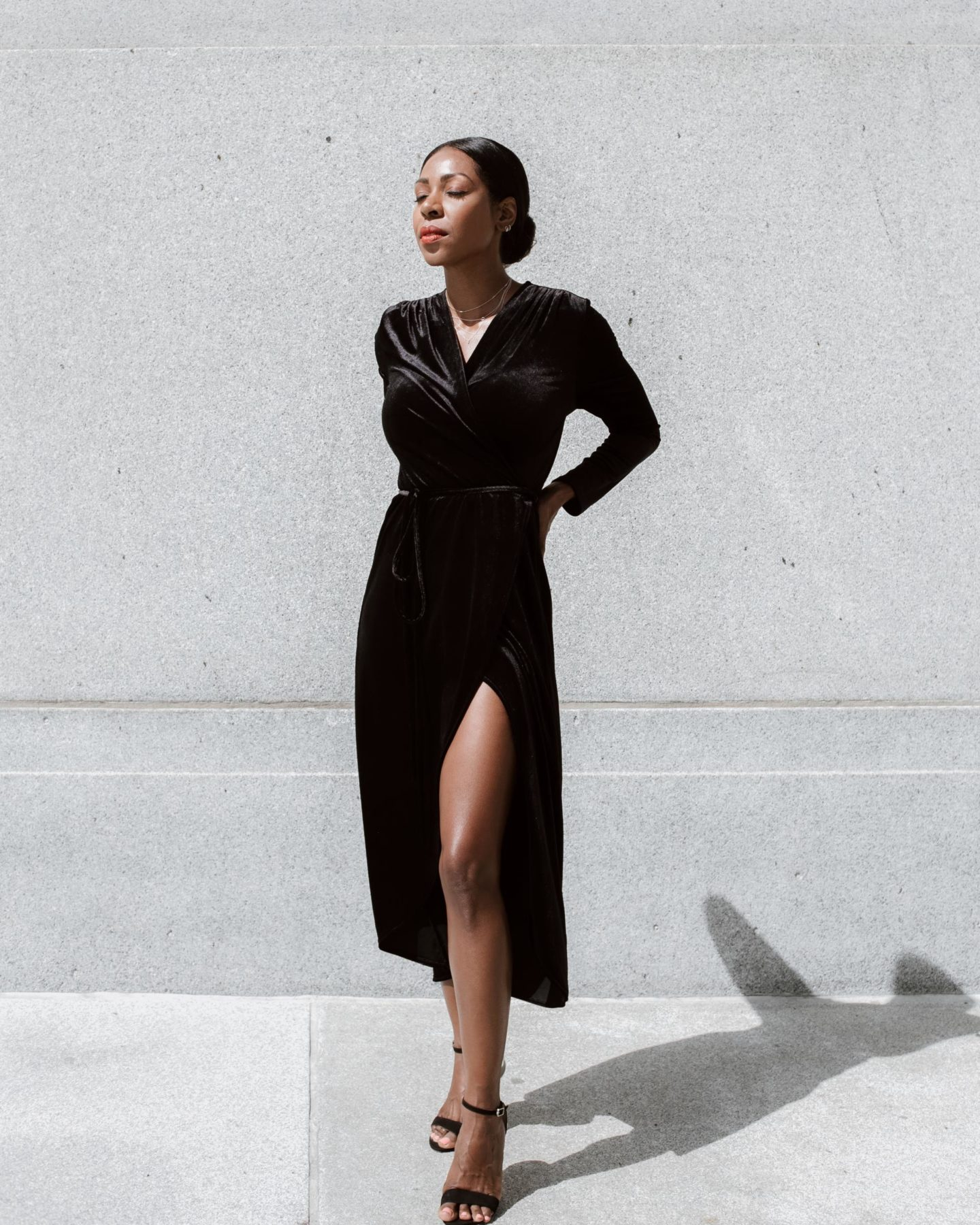 Dominique Baker Wearing a black velvet dress enjoying the sun