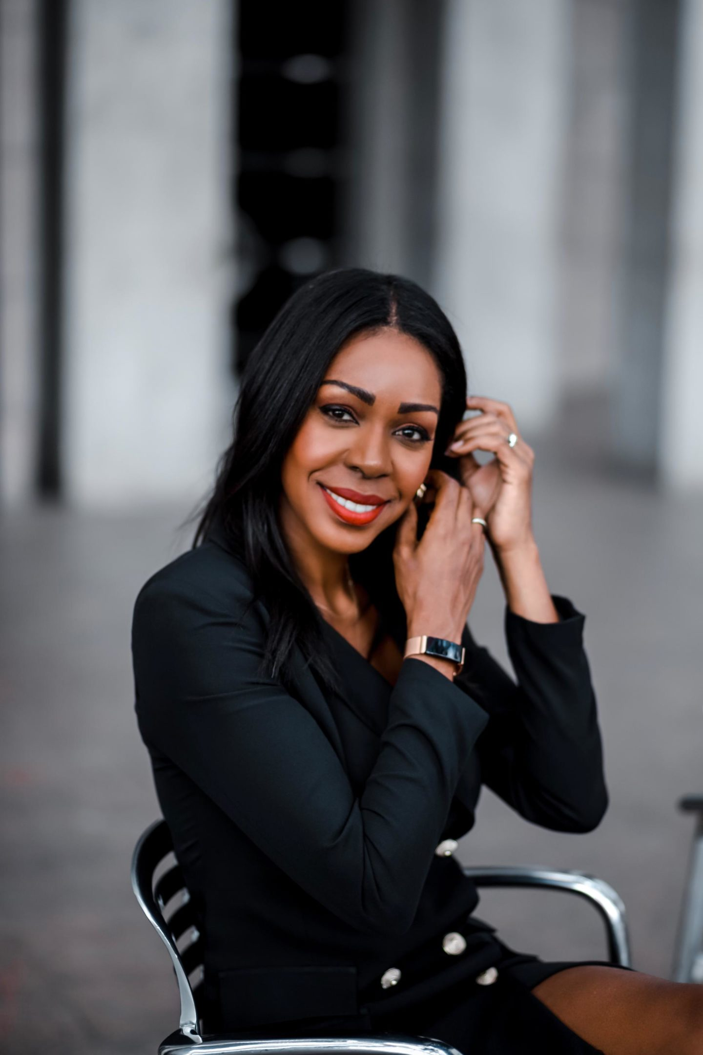 Dominique Baker fixing her earring while wearing the Fitbit Inspire HR Fitness Tracker