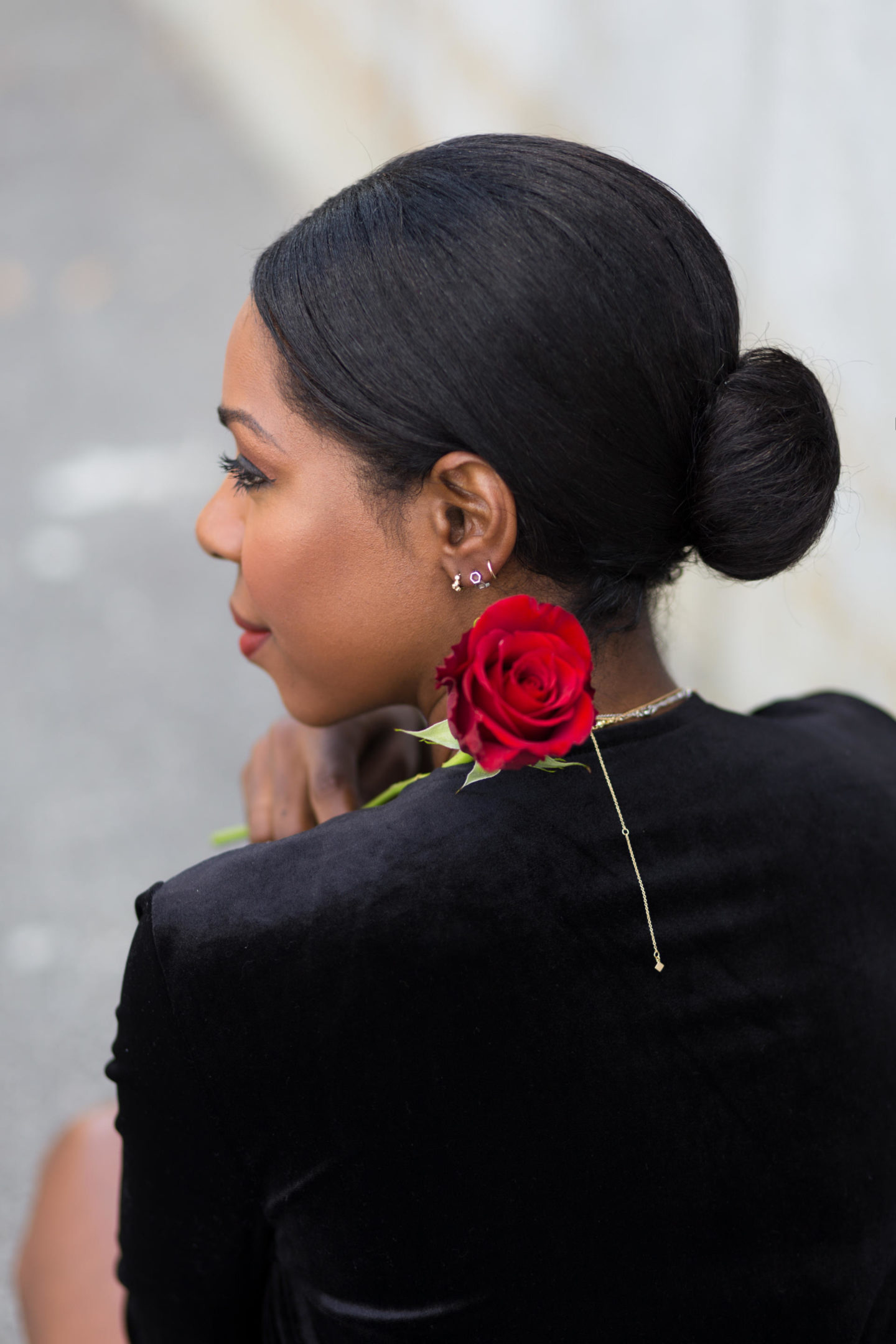 Dominique Baker holding a red rose while wearing a black dress