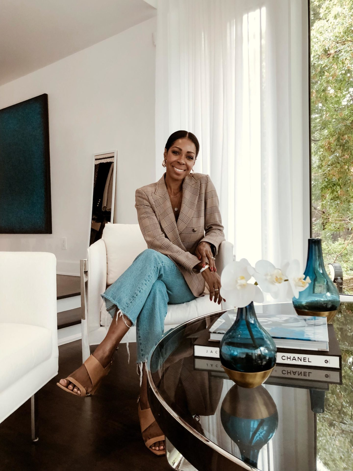 Dominique Baker Sitting down while wearing a blazer and blue jeans