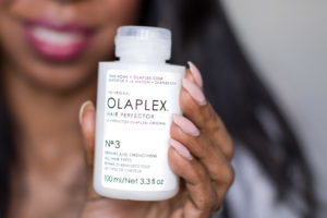 Dominique Baker holding Olaplex No.3 Hair Perfector
