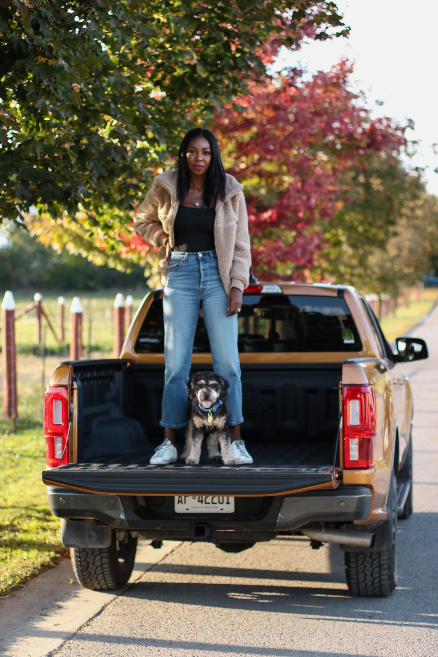 Dominique Baker standing in the cab of the Ford Ranger Lariat with her dog Reese
