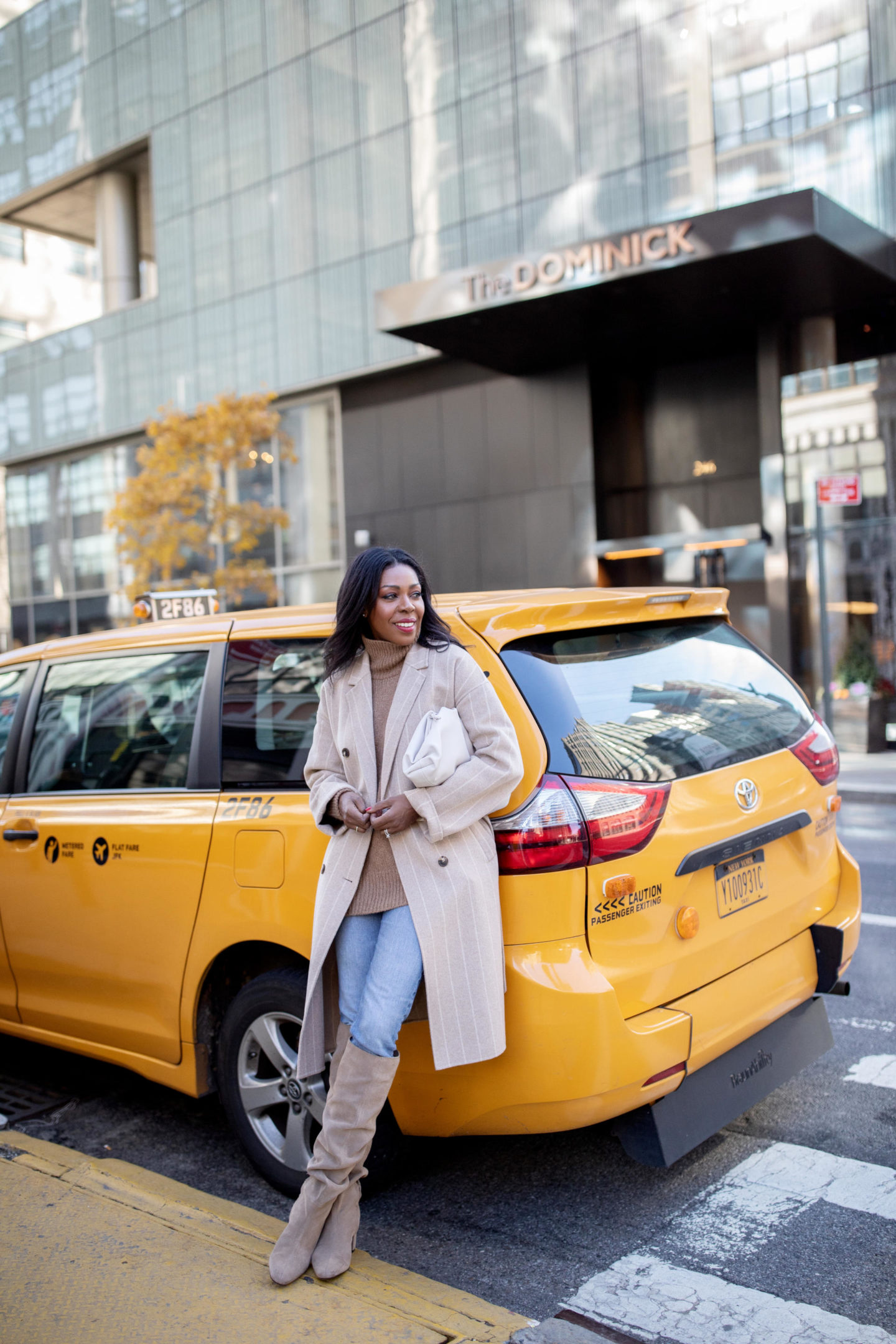 Dominique Baker leaning on a cab in NYC