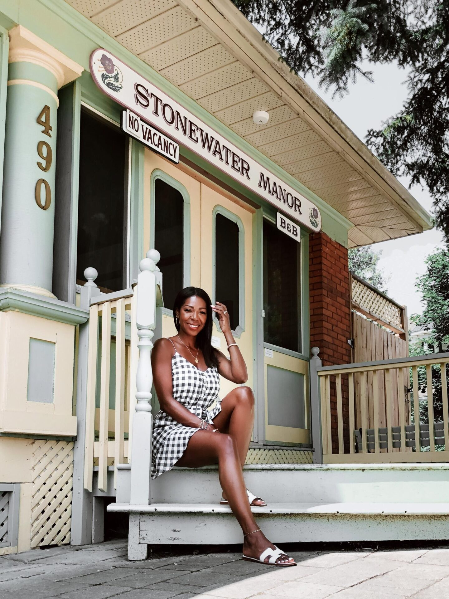 Dominique Baker sitting on porch of the Stonewater B&B Gananoque