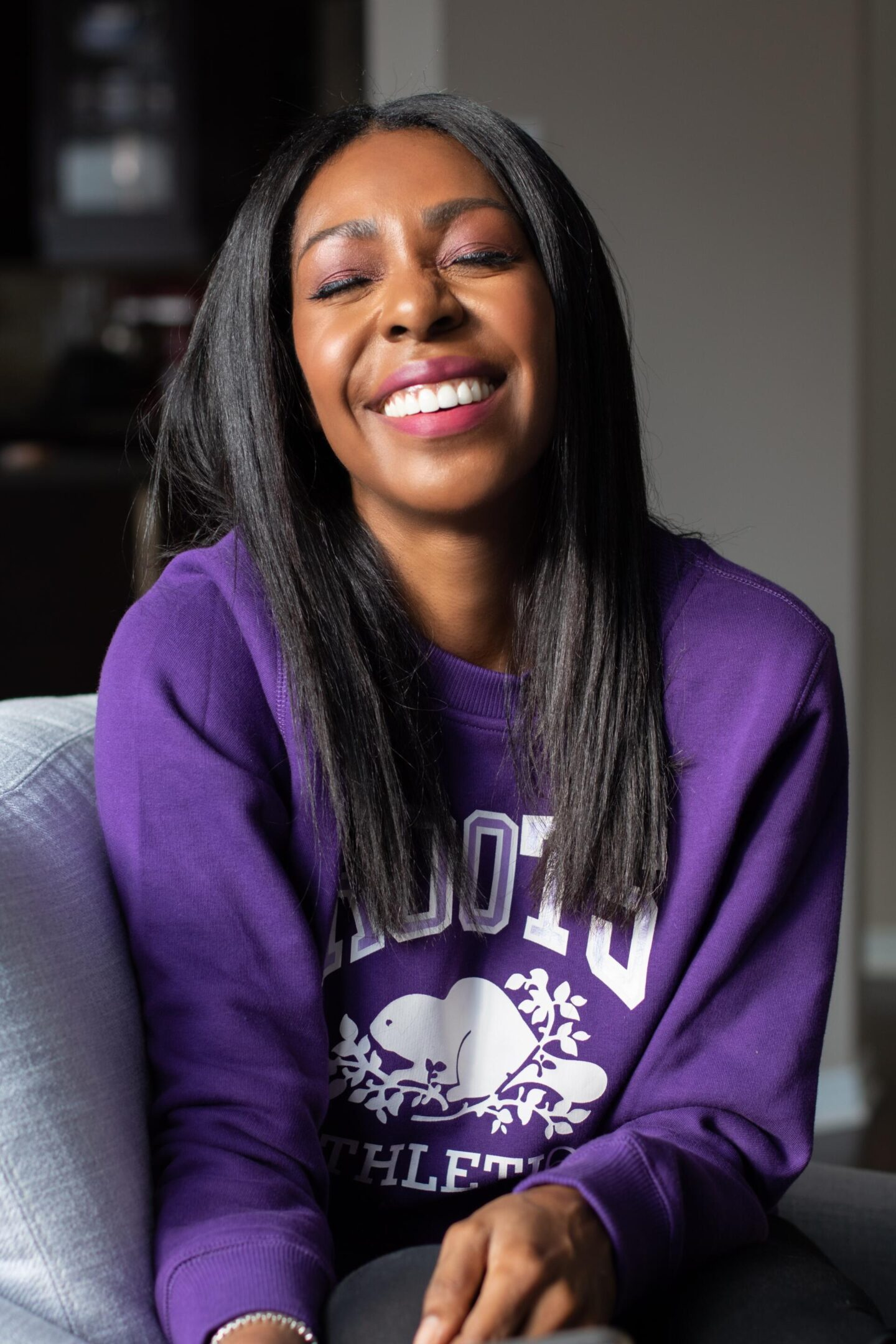 Dominique Baker smiling in a Roots sweatshirt
