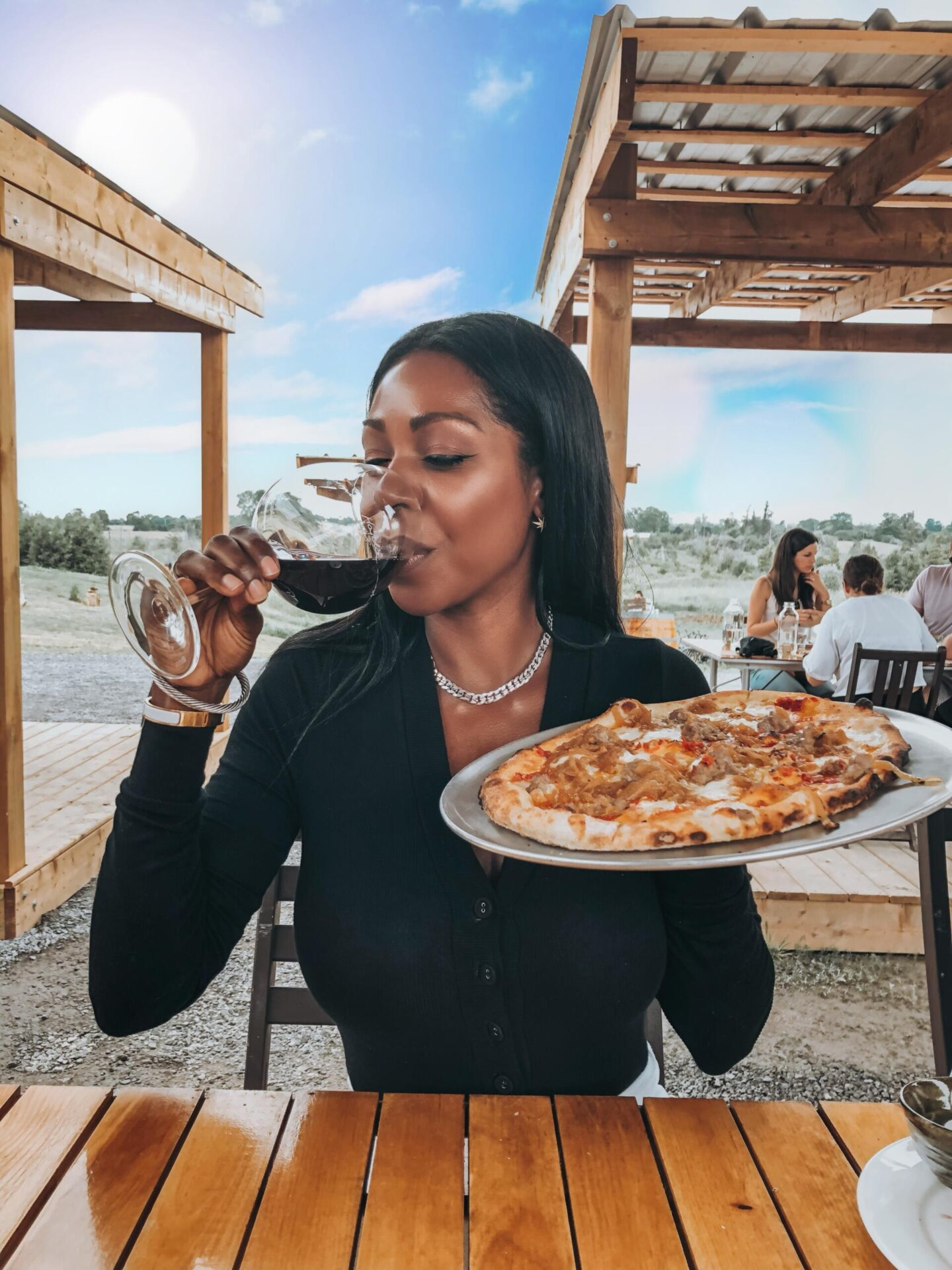 Dominique Baker eating pizza and wine at Norman Hardie Winery