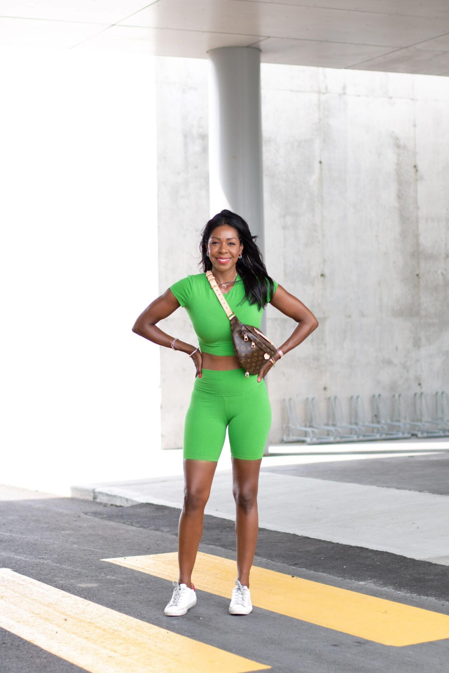 Dominique Baker in Green outfit with Louis Vuitton Bumbag